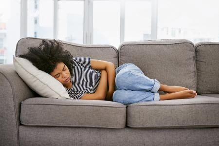 Woman lying on couch with stomach ache